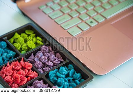 Close Up Allure Thai Handmade Candy In A Brown Plastic Box Next To A Pink Laptop On A White Table Ne