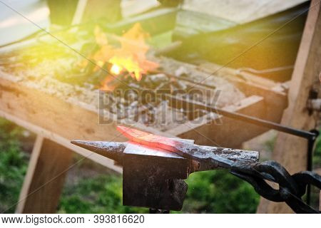 Hot Knife Blade On The Anvil. Workpiece In The Forge On The Background Of The Fire. The Heat From Th