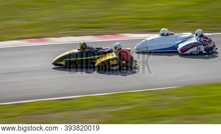 A Panning Shot Of Two Racing Sidecars As They Corner On A Track.