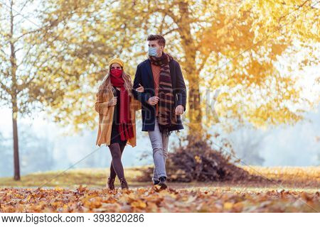 Couple wearing mask walking in autumn park during fall