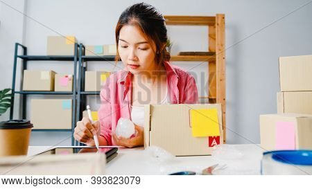 Young Asia Entrepreneur Businesswoman Check Product Purchase Order On Stock And Save To Tablet Compu