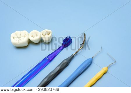 Artificial Teeth With Caries And Toothbrush With Dental Tools Lie On A Blue Background.