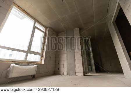 A New Unfinished Apartment Room With The Bare Brick Walls Without Decoration.