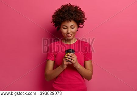 Pleased Curly Woman Holds Paper Cup Of Coffee, Enjoys Leisure Time, Has Break, Drinks Hot Beverage,