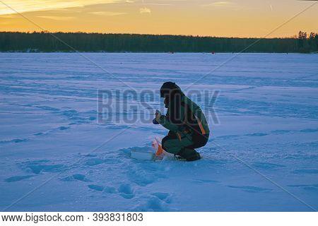 Winter Fishing. The Fishermen Engaged In Ice Fishing