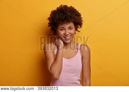 Lovely Young Woman Touches Neck, Looks With Tender Smile, Feels Good And Touched, Wears Casual T Shi