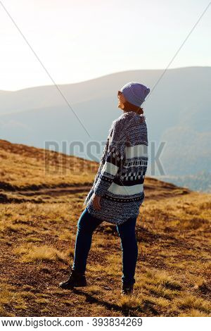Woman Traveler Looking At Sunrise Over The Autumn Mountains. Boho Woman Wearing Hat And Poncho. Fema