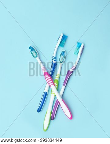 Four Colorful Toothbrushes. Group Of Four Toothbrushes On A Blue Background. The Concept Of Healthy