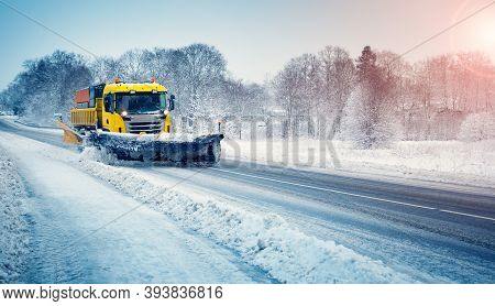Snow Plow Truck Clearing Snowy Road After Snowstorm.