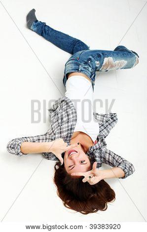 Attraktive Frau macht Frame mit den Händen auf einen weißen Boden liegend