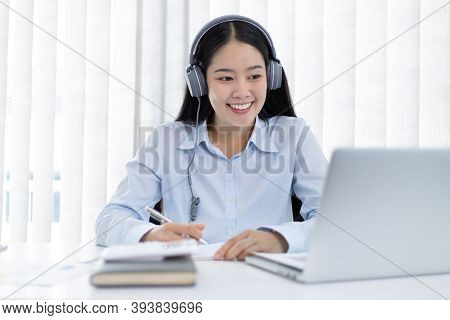 Asian woman is studying online via the internet with a cheerful smile, stay home, New normal, Covid-