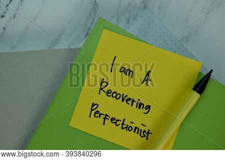 I Am A Recovering Perfectionist Write On Sticky Note Isolated On Wooden Table.