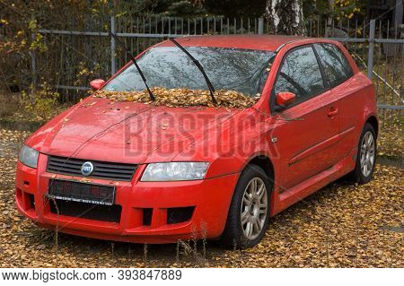 Poznań, Poland November 09.2020: Neglected Abandoned Car In The City Parking Lot. Red Contemporary C