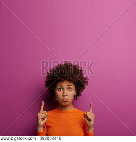 Disappointed Upset Curly Young Woman Points Upside With Index Fingers, Looks Sadly And With Dismay A