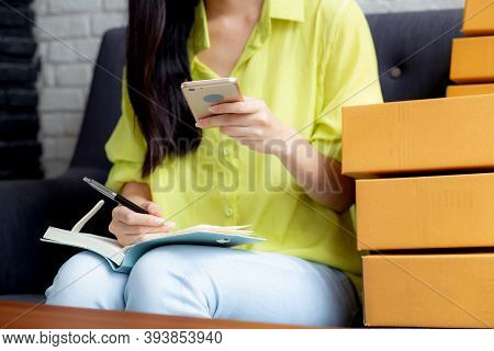 Closeup Young Asian Woman Is Entrepreneur Looking Phone And Writing Order Of Customer With Online On