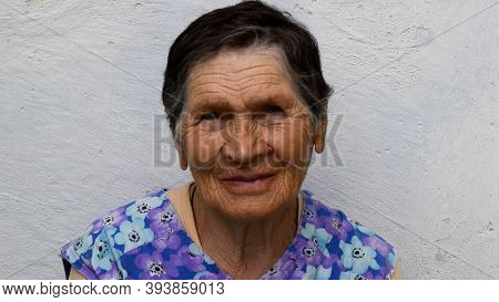 80 Years Old Woman Smile And Look Into Camera. Authentic Senior Woman With Wrinkled Skin Face And Sh