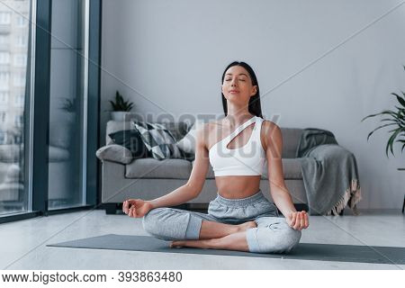 Does Yoga Exercises. Young Woman With Slim Body Shape In Sportswear Have Fitness Day Indoors At Home