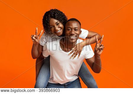 Happy Black Lovers Young Man And Woman Posing On Orange Studio Background, Copy Space. Cheerful Afri