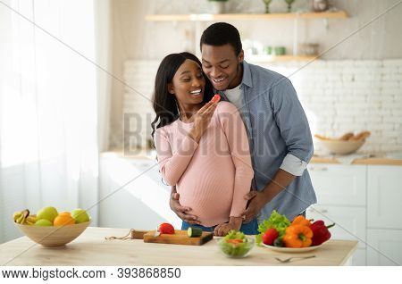 Lovely Black Pregnant Woman Feeding Her Husband With Vegetables While Cooking In Kitchen. Happy Roma