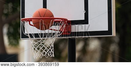 Good Basketball Throw. Basketball Ball Flies Into A Basketball Hoop. Outdoor Basketball Court