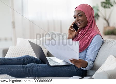 Home Office. Young Black Muslim Freelancer Woman Working With Papers And Laptop In Living Room And T