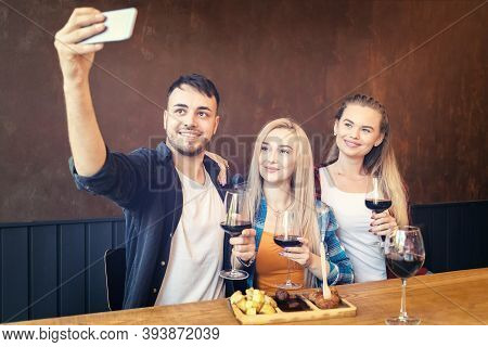 Happy Young Friends Taking Selfie Drinking Wine At Restaurant - Smiling People Having Fun Together A