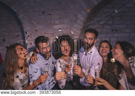 Group Of Friendse Having Fun At New Year's Eve Party, Dancing, Singing, Throwing Confetti And Making