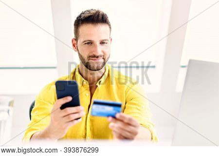 Shot Of Man Holding Credit Card And Mobile Phone In His Hands While Paying Bills With Credit Card.