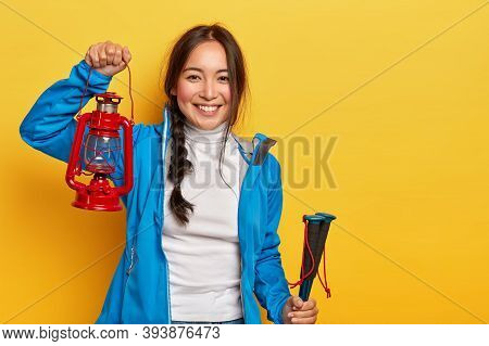 Horizontal Shot Of Cheerful Asian Woman With Dark Plait, Holds Gas Lamp And Trekking Sticks, Dressed