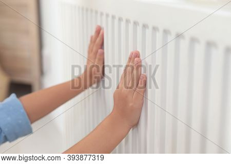 Child Warming Hands On Heating Radiator Indoors, Closeup