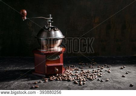 Nostalgic Wooden Coffee Grinder And Roasted Coffee Beans In Side Light Against A Dark Rustic Backgro