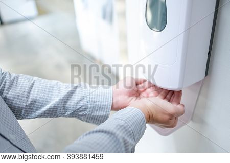 Male Hands Using Automatic Alcohol Dispenser For Cleaning Hand In Office. Infection Prevention Conce