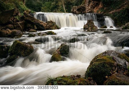 Motion Blur Waterfall Among Trees, Green Leaves, Rocks And Stones In Forest With Cascade River In Be