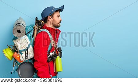 Sideways Shot Of Thoughtful Unshaven Man Wears Hat, Red Jacket, Carries Backpack With Necessary Thin