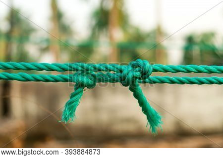 Rope Tie Knot Closeup. Rope With A Two Tied Knot In The Middle Isolated From Background. A Symbol Of