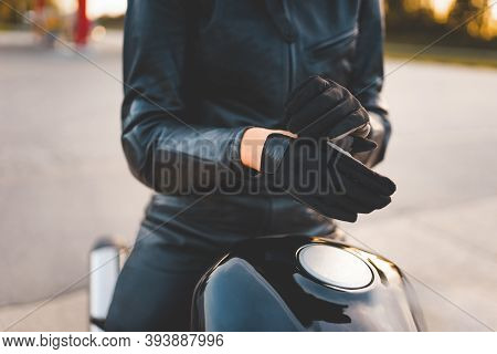 Brutal Girl Motorcyclist Wearing Gloves While Sits On Bike