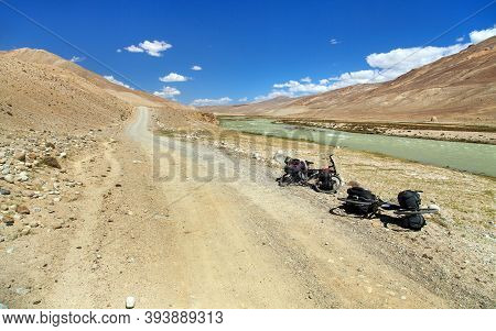Pamir River, Pamir Mountains, Unpaved Road And Two Bicycle. Tajikistan And Afghanistan Border. Pamir