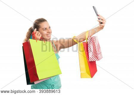 Cheerful Adult Woman Taking Selfie Photo Using Phone Holding Colourful Shopping Bags While Wearing C