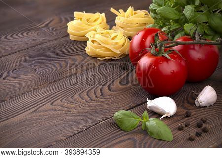 Raw Tagliatelle Pasta With Fresh Basil, Garlic And Branch Of Tomatoes On Rustic Wooden Table