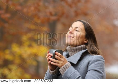 Relaxed Middle Age Woman Holding Coffee Cup Breathing Fresh Ait In Fall Season In A Forest