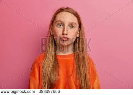Lovely Female Child Makes Funny Expression, Pouts Lips And Gazes At Camera, Has Freckled Face, Dress