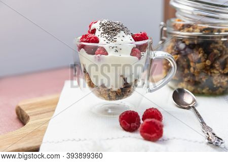 Granola In A Jar And In A Cup With Yogurt And Raspberry. Granola Is A Breakfast Food And Snack Food