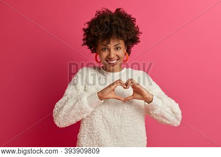 Sincere Happy Dark Skinned Woman Shows Heart Gesture Against Chest, Smiles Positively, Expresses Lov