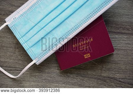 German Passport Reisepass And Medical Face Mask - Travel During Corona Covid-19 Pandemic Concept Fla
