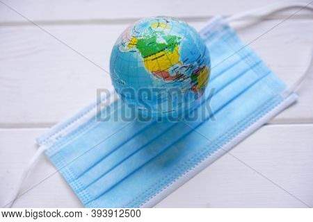 Globe And Medical Face Mask - Global Pandemic - Corona Covid Concept With Selective Focus