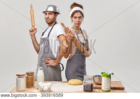 Serious Woman And Man Stand Back To Each Other, Hold Wooden Rolling Pins, Participate In Culinary Ba