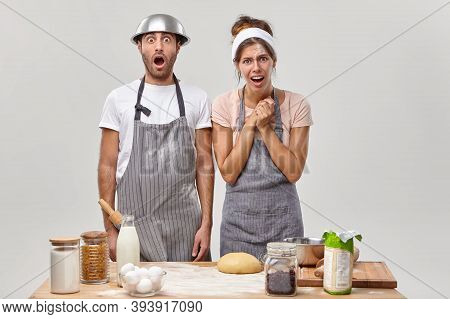 Couple Indoor Prepare Pastry Or Homemade Cookies, Man Looks With Shock, Has Bowl On Head, Indignant