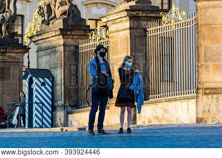 Prague, Czech Republic - September 19, 2020. Tourists With Face Mask In Front Of The Fence To The Pr