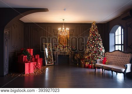 Interior Of Luxury Dark Living Room With Fireplace, Comfortable Sofa And Chandelier Decorated With C
