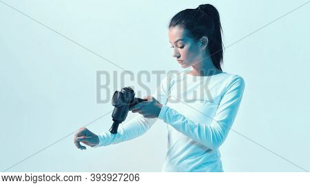 Athletic Young Female Massaging Hand By Handheld Massage Gun In Neon Light, Post-workout Recovery Ro